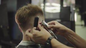 与电剃刀的男性理发 关闭头发整理者发型 理发师做客户的理发在理发店 股票视频