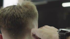 与电剃刀的男性理发 关闭头发整理者发型 理发师做客户的理发在理发店 影视素材