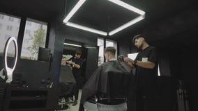 与电剃刀的男性理发 通过使用hairclipper,理发师做客户的理发在理发店 ? 股票录像