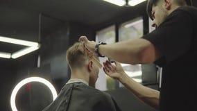 与电剃刀的男性理发 通过使用hairclipper,理发师做客户的理发在理发店 ? 影视素材