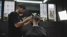与电剃刀的男性理发 通过使用hairclipper,理发师做客户的理发在理发店 ? 股票视频