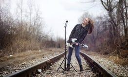 与电吉他的美丽的女孩摇摆物 岩石musicia 库存照片