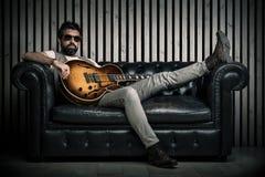 与电吉他的成人白种人吉他弹奏者画象坐葡萄酒沙发 音乐在长沙发的歌手概念和 免版税库存图片