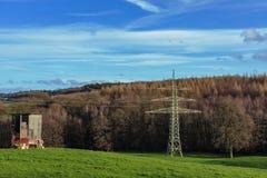 与电子塔的森林和middow风景 免版税图库摄影
