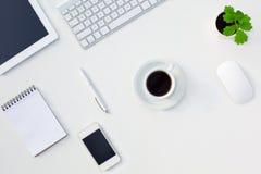 与电子小配件和文具咖啡杯和花的白色办公桌表 免版税库存照片