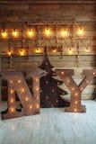 与电灯泡光和圣诞树的木信件NY在木墙壁背景 顶楼想法 圣诞节概念查出的新的空白年 新的Yo 免版税库存图片