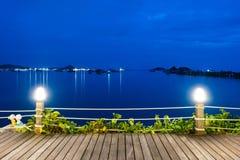 与电灯泡岗位的木板条地板在海和码头背景 免版税图库摄影