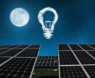 与电灯泡的太阳电池板从云彩在夜 免版税库存图片