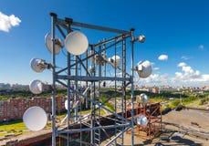 与电视天线、卫星盘、微波和移动运营商盘区天线的电信塔位于屋顶 图库摄影
