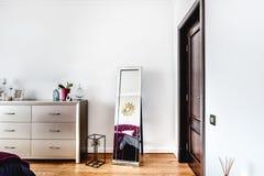 与电视立场、扶手椅子和镜子的明亮的卧室设计作为装饰 库存照片