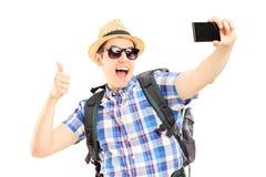 与电话和给的男性旅游为照相的himselves 免版税图库摄影
