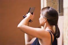 与电话照相机的少妇射击 免版税库存照片