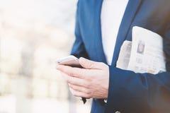与电话的商人在手中 库存图片