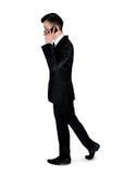 与电话的商人步行 免版税库存图片