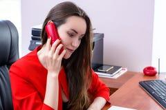 与电话的年轻女商人谈话 库存照片