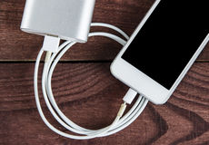 与电话的残破的充电的在木表上的缆绳和Powerbank 免版税库存照片