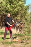 与电锯的人切口 在农场的工作 加热的木准备 伐木工人与锯一起使用 免版税库存图片