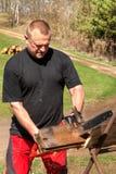 与电锯的人切口 在农场的工作 加热的木准备 伐木工人与锯一起使用 图库摄影