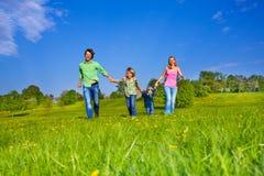 与男孩的愉快的父母步行在公园 免版税库存照片