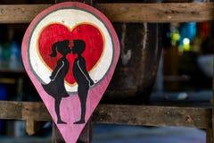 与男孩的标志板和女孩亲吻和红心 库存照片