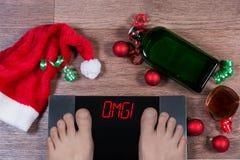 与男性脚的数字式标度在他们和标志由圣诞节装饰、瓶和杯alcohl omgsurrounded 免版税库存图片