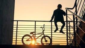 与男性青年期开会的楼梯栏杆对此和他的在他旁边的自行车 影视素材