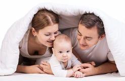 与男婴的年轻家庭在床上的毯子下 库存照片