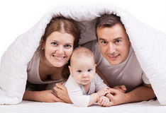 与男婴的年轻家庭在床上的毯子下 图库摄影