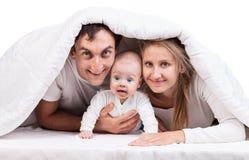 与男婴的年轻家庭在毯子下 库存图片