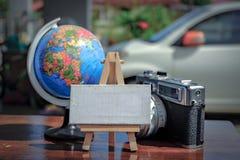 与画架、地球和葡萄酒照相机布局的白色帆布在木书桌上在白天 选择聚焦射击和退色的作用 库存图片