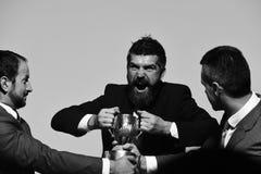 与疯狂的面孔的商人在灰色背景的正式衣服 工友或伙伴战斗为赢取的竞争 图库摄影