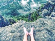 与疲乏的远足者腿的岩石没有鞋子 赤裸男性腿 库存照片