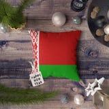 与白俄罗斯旗子的新年快乐标记在枕头 在木桌上的圣诞装饰概念与可爱的对象 E 免版税图库摄影