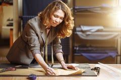 与白垩在缝合的车间和看照相机的专业成年女性裁缝标号布料样式 免版税图库摄影