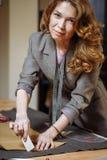 与白垩的专业成年女性裁缝标号布料样式在演播室 免版税库存照片
