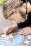 与白垩的女孩图画在路面 免版税库存照片