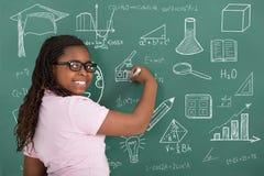 与白垩的女孩文字在绿色黑板 免版税库存照片