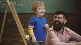 与白垩的小男孩图画在黑板 幼儿期教育和使用概念   ?? 股票视频