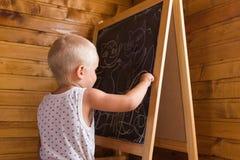 与白垩的小男孩图画在黑板 库存照片