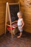 与白垩的小男孩图画在黑板 库存图片