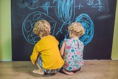 与白垩的男孩和女孩油漆在黑板 库存照片