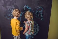 与白垩的男孩和女孩油漆在黑板 免版税库存图片