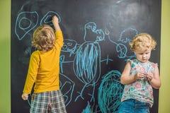 与白垩的男孩和女孩油漆在黑板 库存图片
