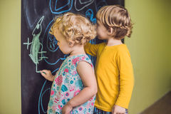 与白垩的男孩和女孩油漆在黑板 免版税库存照片