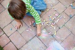 与白垩的男孩绘画 免版税库存图片