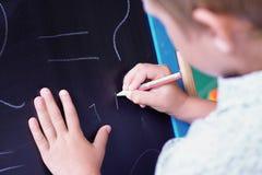 与白垩的逗人喜爱的白种人小男孩油漆在黑板 免版税库存照片