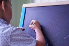 与白垩的逗人喜爱的白种人小男孩油漆在黑板 免版税库存图片