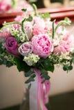 与白玫瑰、绯红色牡丹和绿色的土气婚礼花束在一个木地板上 户内 免版税库存照片