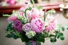 与白玫瑰、绯红色牡丹和绿色的土气婚礼花束在一个木地板上 户内 库存照片