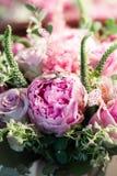 与白玫瑰、绯红色牡丹和绿色的土气婚礼花束在一个木地板上 户内 免版税库存图片